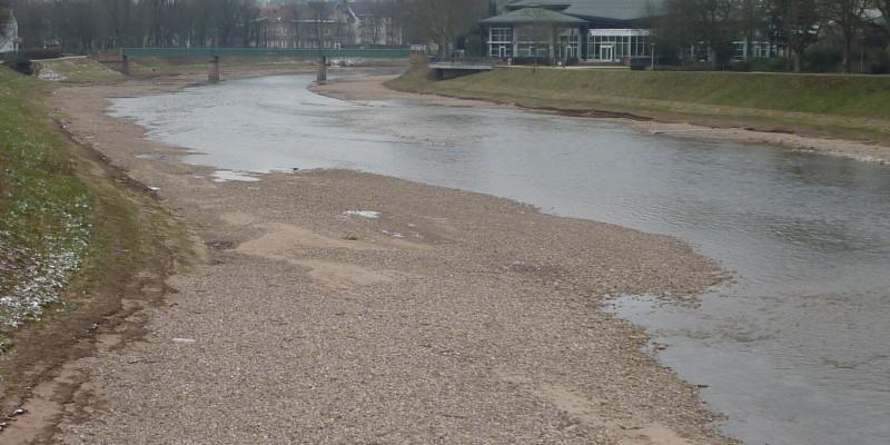 Foto: Ein Abschnitt der Murg kurz nach der Renaturierung. Entlang der Ufer des Gewässers wurde Kies eingebracht, der die eigendynamische Entwicklung des Flusses anregen soll. Eine Kiesbank reicht bis weit in das Gewässer hinein.