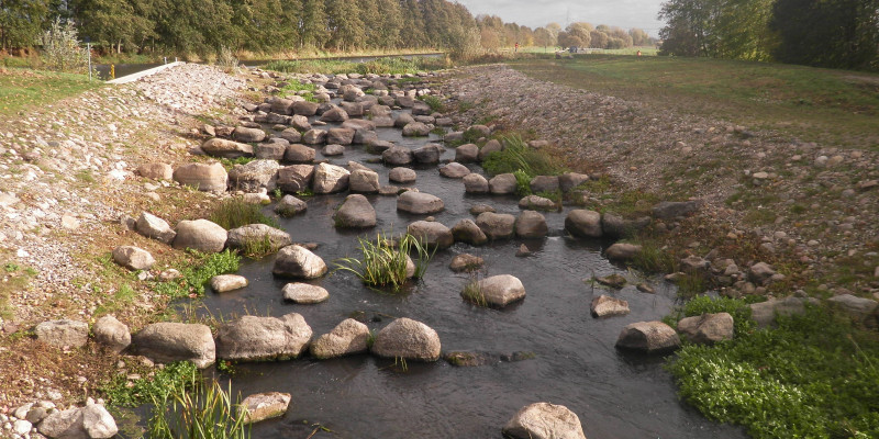 Foto: Die fertiggestellte Fischaufstiegsanlage in Lüssow. Eine langgezogene Gleite mit vielen größeren Steinblöcke im Gewässer ersetzt das alte Streichwehr.
