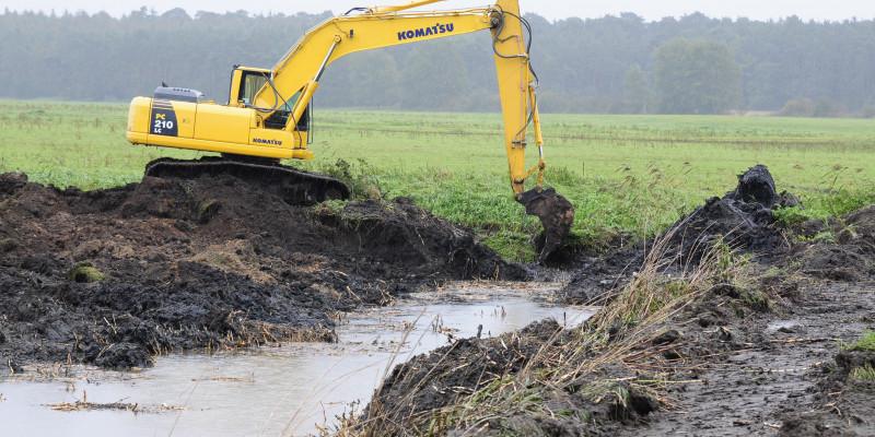 Foto: Die Alte Nebel während der Bauarbeiten. Ein Bagger steht am Gewässerufer und konstruiert den neuen Gewässerverlauf. Im Hintergrund liegen Ackerflächen und Wald.