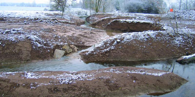Foto: Der neu angelegte, stark geschwungene Verlauf der Wern in winterlicher Landschaft.