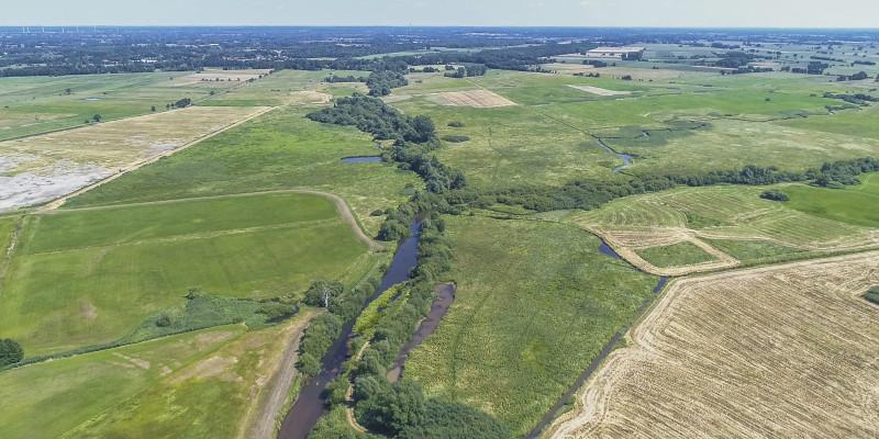 Luftbild der Wümme mit durchgehendem Gehölzsaum umgeben von landwirtschaftlich genutzten Grünlandflächen