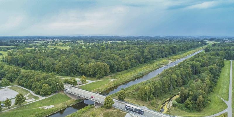Luftbild des Flusses Murg bei Rastatt. Entlang des geradlinigen Hauptgerinnes liegt ein strukturreiches Nebengerinne, das als Überflütungsfläche für Hochwasser dient. Im Hintergrund liegen ausgedehnte Auwaldflächen. Am Bildrand stehen Gebäude der Stadt.