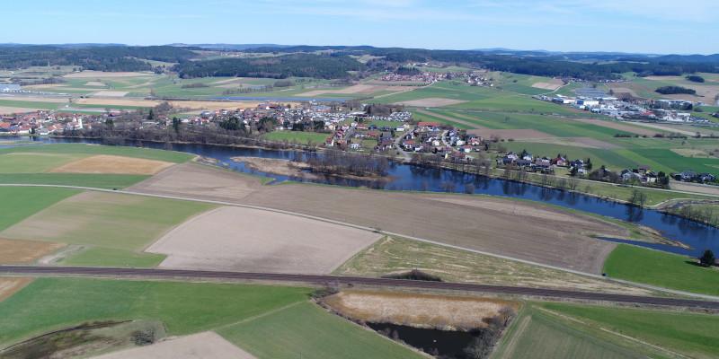 Luftbildaufnahme des Flusses Naab mit Grünland- und Ackerflächen, die bis an die Gewässerkante reichen. Parallel zum Fluss verlaufen auf beiden Seiten Verkehrswege.