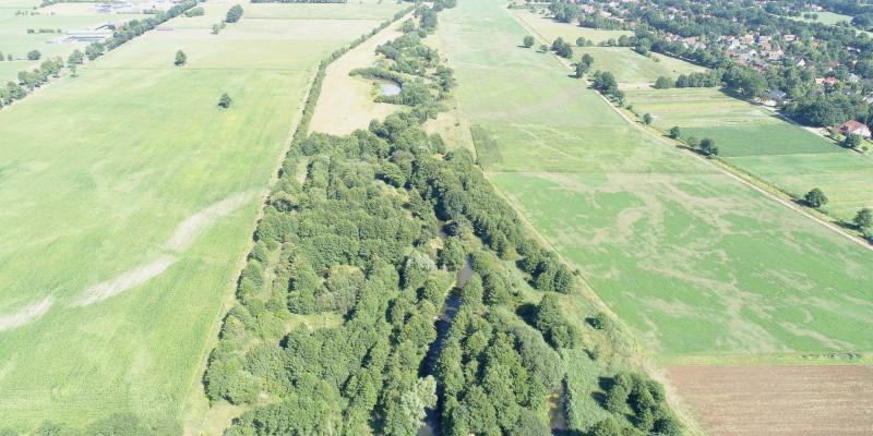Luftbildaufnahme des sehr breiten Entwicklungskorridors mit Bäumen und Sträuchern, der den Fluss Wümme von landwirtschaftlichen Flächen und Grünland abgrenzt.