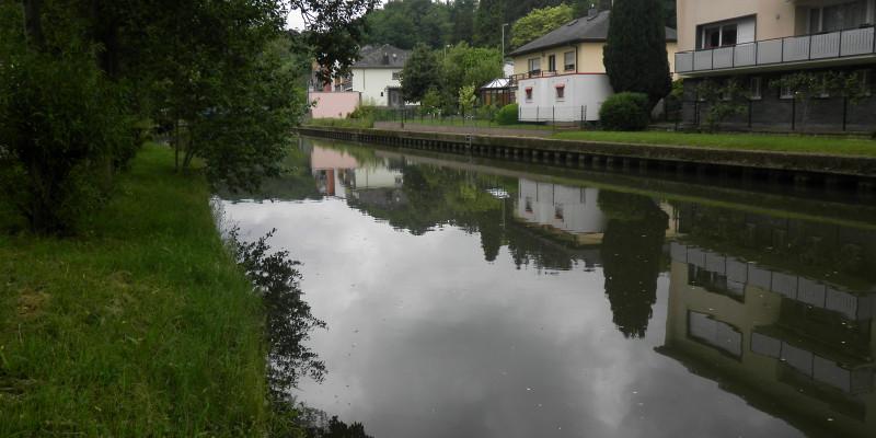 Foto: Ein begradigter Fluss mit Ufersicherung und einseitig mit Häusern, die bis auf wenige Meter an den Gewässerrand reichen.