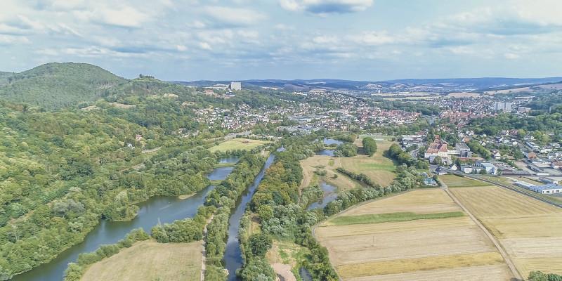 Luftbild der Fulda mit Nebengewässern und großräumigen Auenflächen. Entlang des Gewässers wachsen breite Randstreifen, an die landwirtschaftliche Flächen angrenzen. Im Hintergrund liegen Siedlungsflächen.