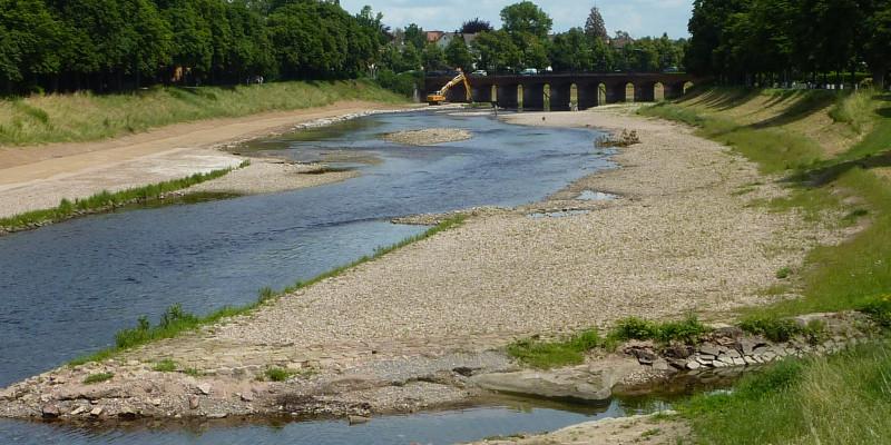 Foto: Ein renaturierter Gewässerabschnitt mit ausladenden Kiesbänken. Noch sind die Ufer vegetationsfrei. Im Hintergrund steht ein Bagger an einer Brücke.