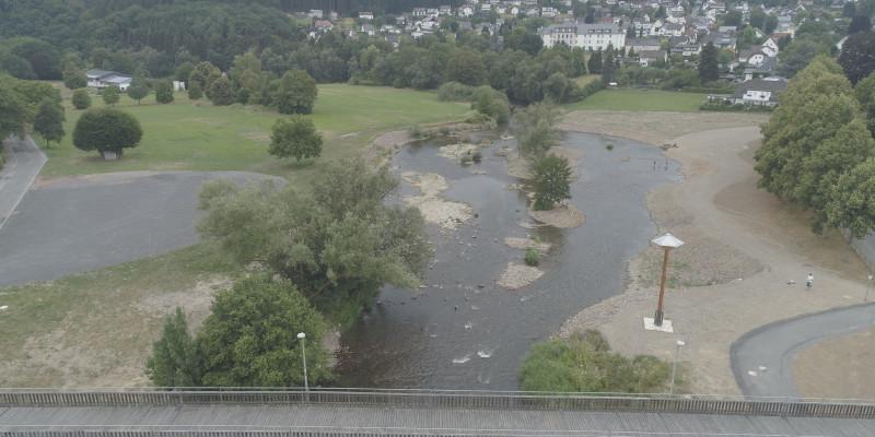 Luftaufnahme eines renaturierten Gewässers. Unter einer Brücke strömt ein breiter Fluss mit vielen kleinen Inseln aus Kies und Vegetation. An das Gewässer grenzt ein kleiner, unbefestigter Weg an und im Hintergrund ist eine größere Siedlung erkennbar.