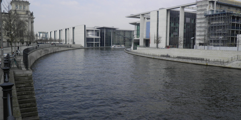 The Spree in Berlin with government buildings in the background. The riverbank is fully concreted, with paths running along the bank.