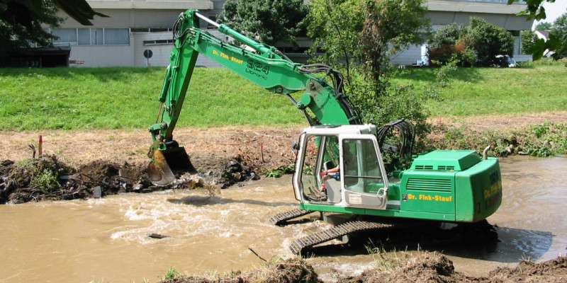 An excavator working the banks of a watercourse.