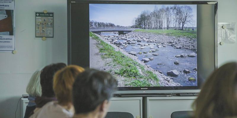Foto: In einem Konferenzzimmer schauen mehrere Menschen auf einen Bildschirm, auf dem ein Bild einer Renaturierung gezeigt wird.