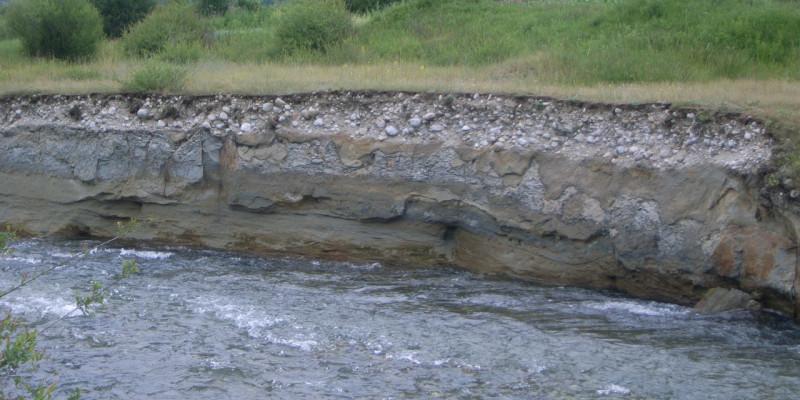 Foto: Ein Uferabbruch, an dem der unter der Vegetationsdecke liegende Schotterkörper sichtbar wird.