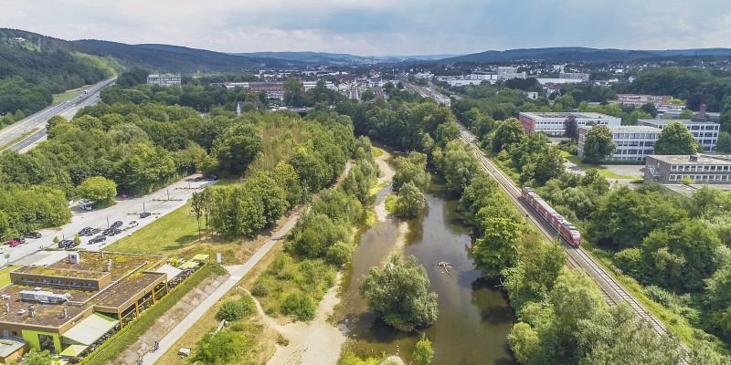 Luftbildaufnahme der renaturierten Ruhr, die umgeben ist von Häusern, Straßen und einer Bahnlinie. Ein Ausflugslokal bietet direkten Blick auf die Renaturierung. Im Fluss selbst liegen Kiesbänke und Totholz. Der Uferbereich ist mit zahlreichen Gehölzen bewachsen.