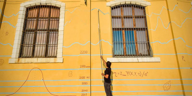 Das Foto zeigt den Künstler Andreco bei der Bemalung einer Hauswand in Venedig. Die Hauswand trägt bereits einige fiktive Hochwassermarken bis 2100. Das Bild visualisiert das Risiko des globalen Meeresspiegelanstiegs für den Menschen jenseits einer globalen Erwärmung auf 1,5 °C.