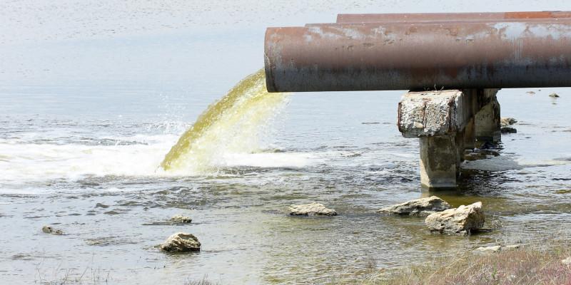 Foto: Ein Rohr, das Abwasser in einen Fluss einleitet. Im Bereich der Einleitung bildet sich Schaum.