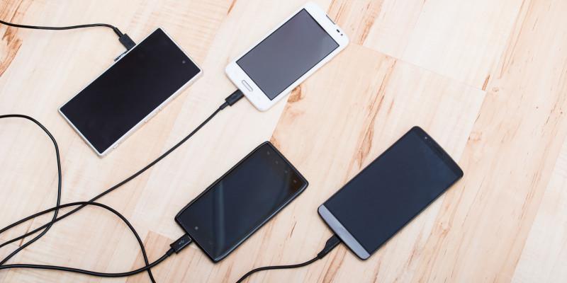 Smartphones hängen an Ladekabeln