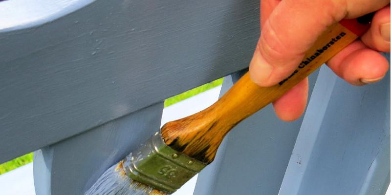 Eine Bank wird mit Holzschutzmittel bestrichen