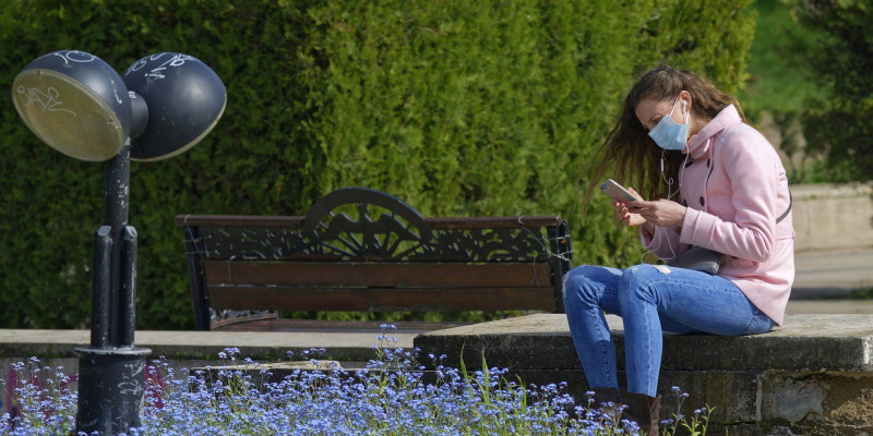Eine Frau sitzt in einem Park auf einer Bank, trägt einen Mund-Nasen-Schutz und schaut auf ihr Smartphone
