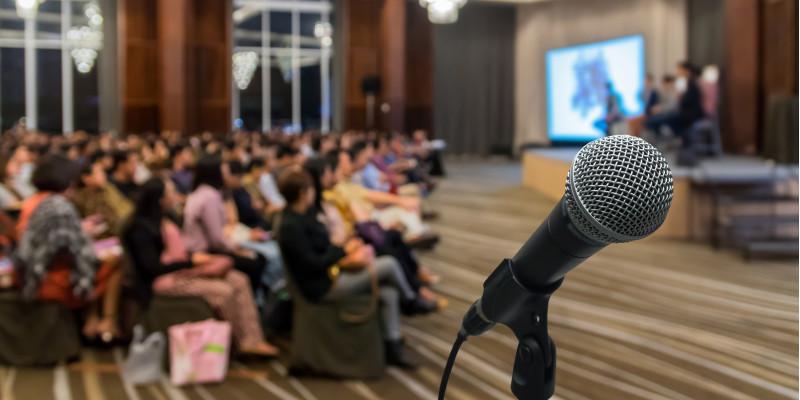 Mikrofon in einem Ständer, im Hintergrund ein Saal mit Zuhörern