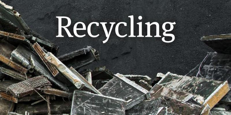 Das Wort Recycling vor schwarzem Hintergrund, darauf auch ausrangierte Kühlaggregate.
