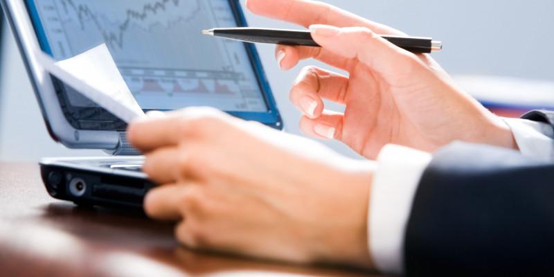 Hände vor einem PC-Bildschirm, auf dem eine Börsenkurze erscheint.