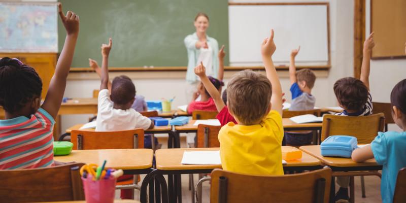 Schülerinnen und Schüler sitzen in einer Schulklasse und melden sich. Vorne ist die Lehrerin an der Tafel zu sehen.