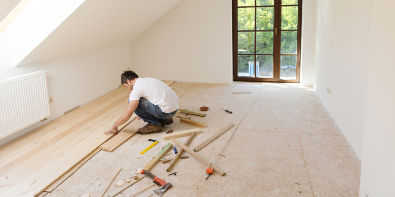 A craftsman laying a wooden floor.