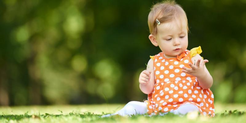Ein Kleinkind auf einer Wiese.