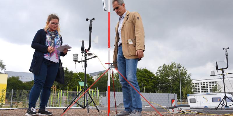 Eine Frau und ein Mann nehmen Daten eines Messgerätes auf einem Flachdach