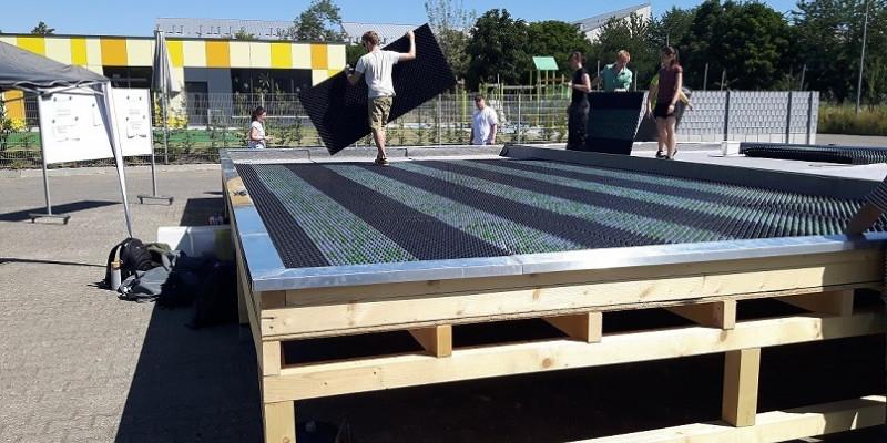 Studierende verlegen Bodenplatten auf einem Holzgerüst.