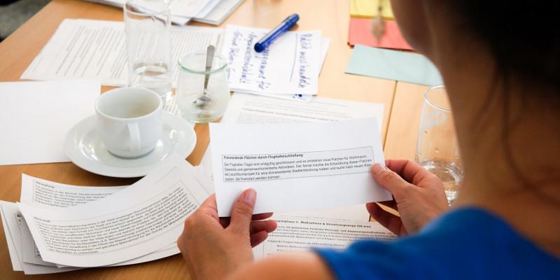 Eine Frau sitzt an einem Gruppentisch und hält eine Zettelstück
