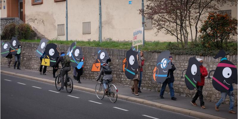 Teilnehmende tragen EMW-Maskottchen Edgar durch Würzburg