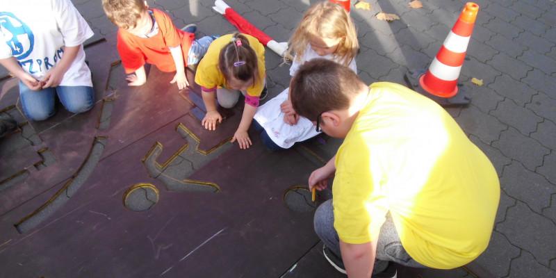 Kinder zeichnen die Umrisse des Verkehrsschilds auf den Boden