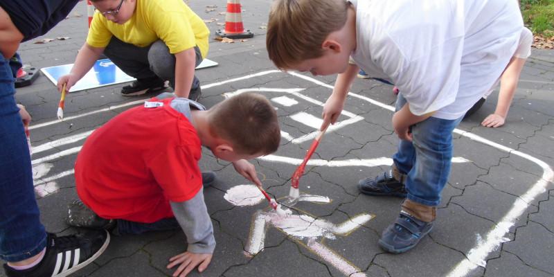 Kinder malen ihr Verkehrszeichen auf den Boden