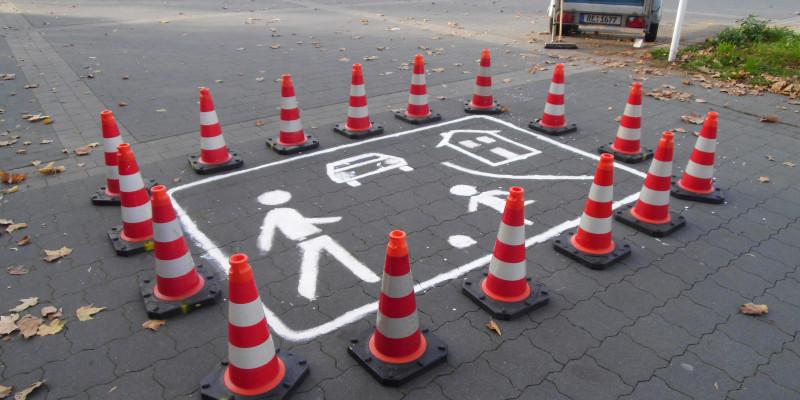 Leitkegel schützen das frisch gemalte Verkehrszeichen