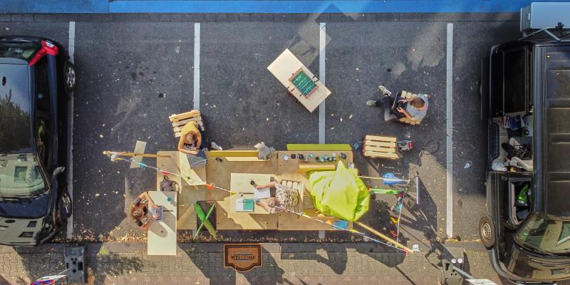 Auf einem Parkplatz steht ein großes Gefährt quer und Menschen sind aus der Vogelperspektive zu sehen, die im Freien an ihren Laptops arbeiten.