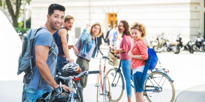 Menschen stehen mit ihren Fahrrädern in der Stadt