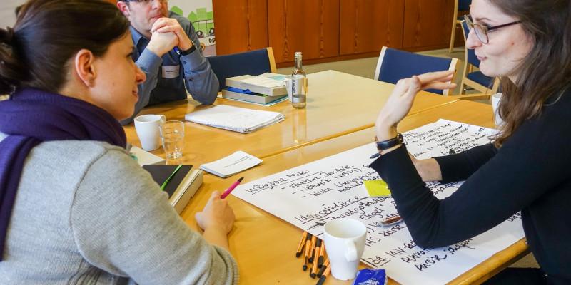 Workshopteilnehmende diskutieren und arbeiten zusammen