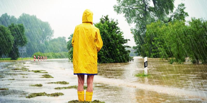 Frau steht mit Regenjacke und Gummistiefeln in einem überschwemmten Gebiet