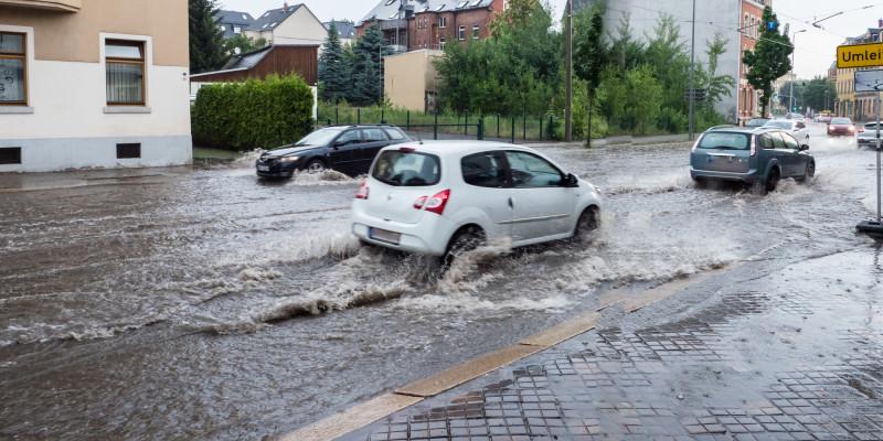 Auto fährt überflutete Straße entlang