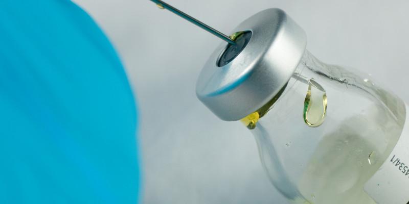 Foto einer Arzneimittelflasche an der eine Spritze aufgezogen wird.