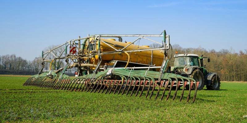 Traktor mit Gülletank und Schleppschlauch auf landwirtschaftlicher Nutzfläche
