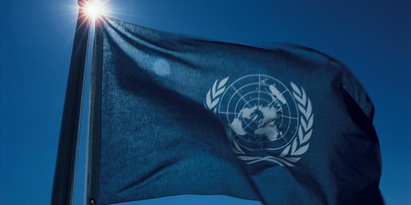 Wehende Flagge der Vereinten Nationen vor blauem Himmel
