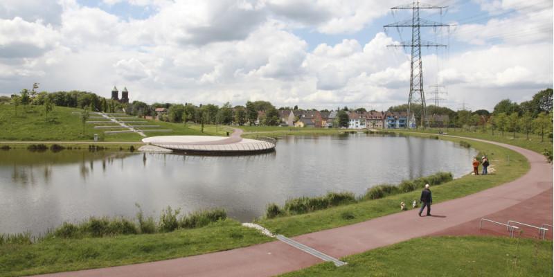 Grünfläche mit See, im Hintergrund ist ein Wohngebiet zu erkennen, Menschen spazieren am See entlang