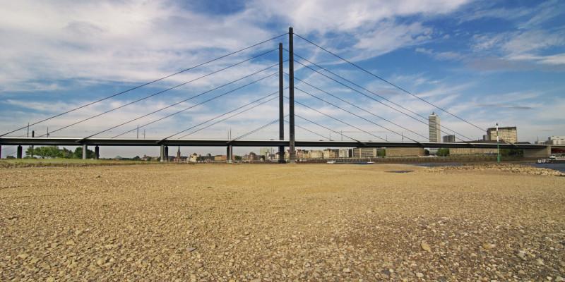 Eine Autobrücke führt über einen teils ausgetrockneten Fluß.