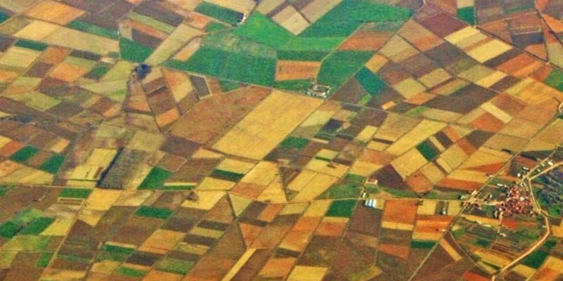 Vogelperspektive auf geometrisch angelegte und sehr farbig wirkende Ackerstrukturen mit Siedlungen