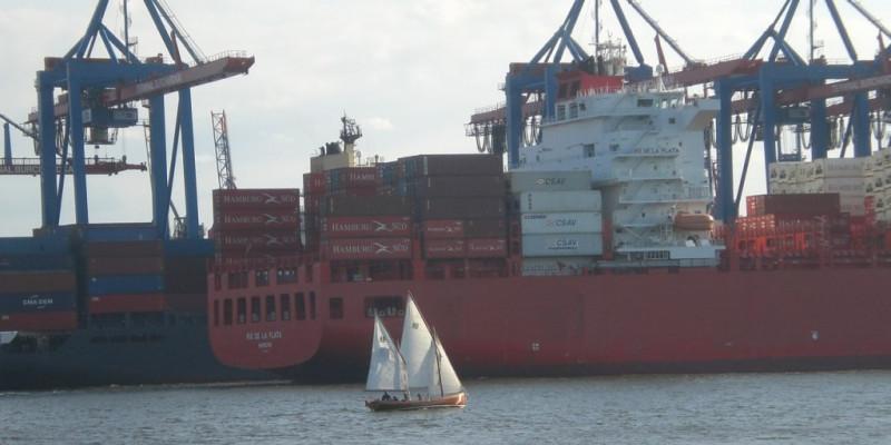 Kleines Segelschiff vor einem Containerschiff im Hamburger Hafen
