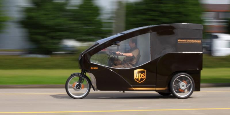 Ein Lastenrad eines Paketdienstes fährt auf einer Straße.