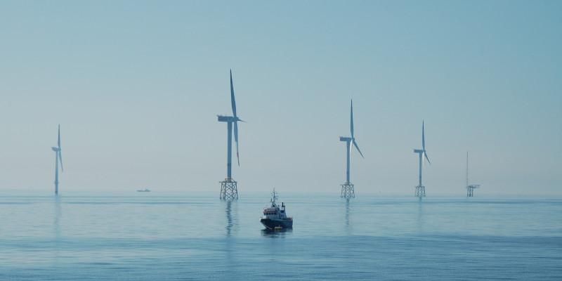 Das Bild zeigt im Meer stehende Windräder eines Offshore-Windparks und ein dazwischen schwimmendes Schiff.