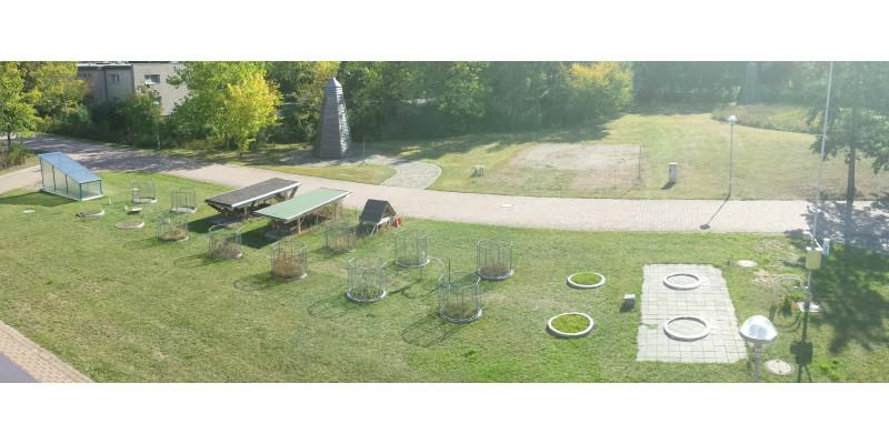 Rasenfläche mit rund umzäunten Flächen.